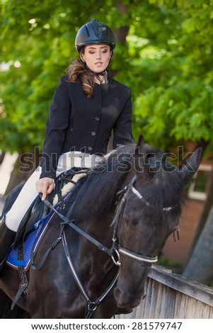 beautiful young woman riding her black horse