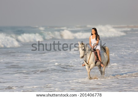 beautiful young woman riding horse on beach - stock photo