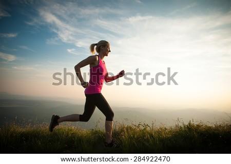 beautiful young woman run on a mountian path at sunrise - stock photo