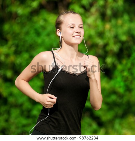 Beautiful young woman running in green park on sunny summer day - stock photo