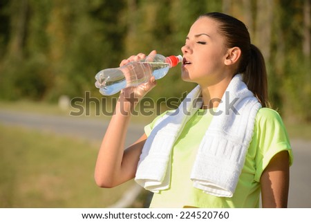 Beautiful young woman running in green park on sunny summer morning - stock photo