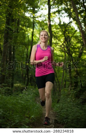 Beautiful young woman running on forest  path