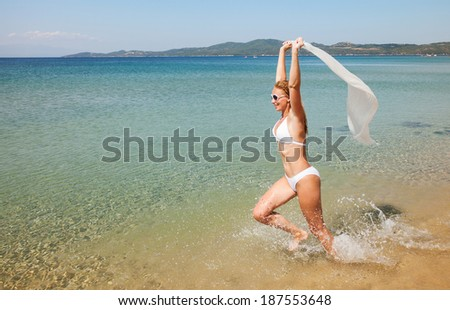 Beautiful Young woman running on the beach and holding white scarf.