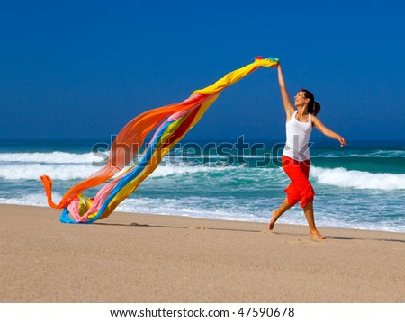 Beautiful young woman running on the beach with a colored tissue - stock photo