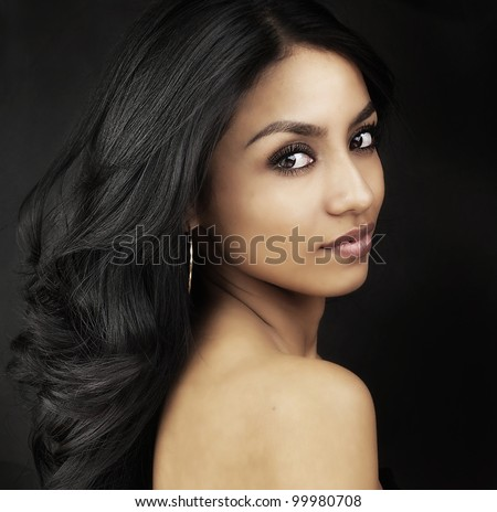 Beautiful young woman's face and long dark shiny hair. - stock photo