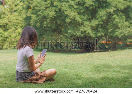 Beautiful young woman's hand using smart phone in the park , copy space