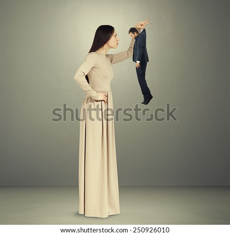 beautiful young woman scrutinizing small man in black suit over grey background - stock photo