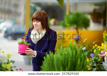 Beautiful young woman selecting flowers at flower market in Paris, France - stock photo