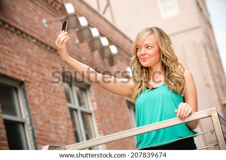 Beautiful Young Woman Selfie - This is a shot of a beautiful young woman taking a selfie of herself in a downtown city setting. - stock photo