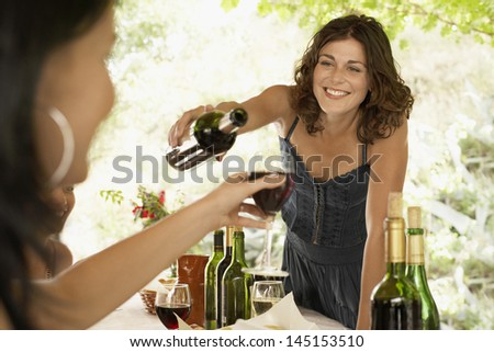 Beautiful young woman serving red wine to female friend in party - stock photo