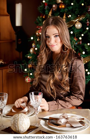 Beautiful young woman setting the Chrtismas table