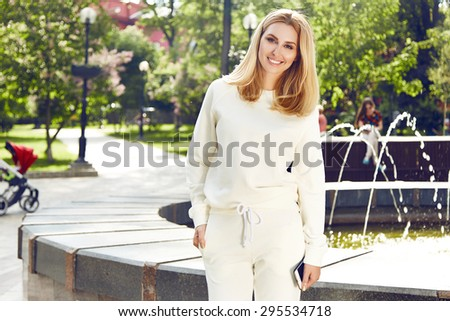 Beautiful young woman sexy blonde girl with make-up walks in the park, doing exercises, sports, yoga or gymnastics dressed in light tracksuit or pleasure spring summer nature sunny warm morning smile