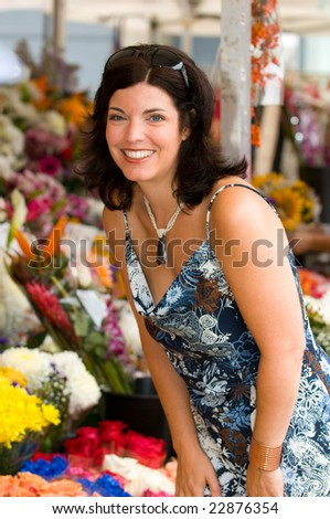 Beautiful Young Woman Shopping At An Outdoor Flower Market - stock photo