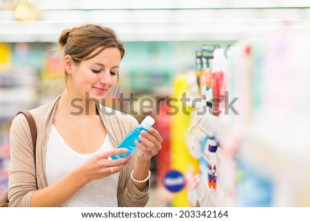 Beautiful young woman shopping for cosmetics in a grocery store/supermarket (color toned image) - stock photo