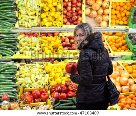 Beautiful young woman shopping for fruits and vegetables at a supermarket - stock photo