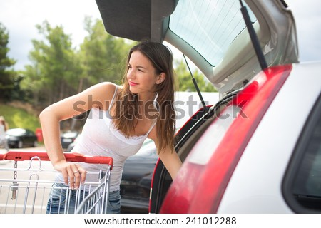 Beautiful young woman shopping in a grocery store/supermarket (color toned image), putting the groceries into her car in the parking lot, looking around - stock photo