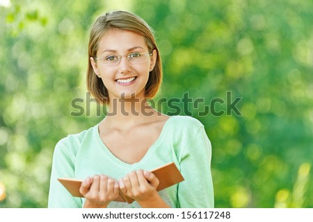 beautiful young woman short hair glasses read book park - stock photo