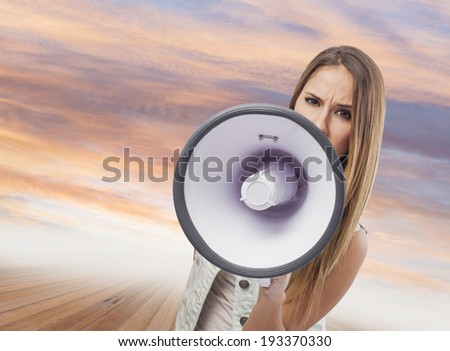 beautiful young woman shouting with a megaphone - stock photo