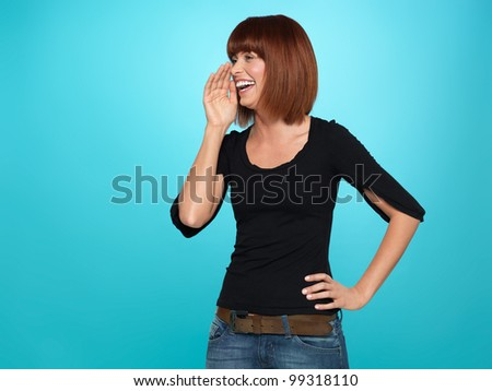 beautiful, young woman shouting with her hand near her mouth, on blue background