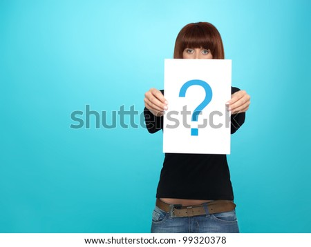 beautiful, young woman showing a question mark on a white piece of paper, on blue background - stock photo