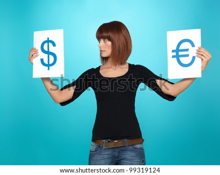 beautiful, young woman showing and comparing a dollar and an euro symbol, on two pieces of paper, on blue background - stock photo