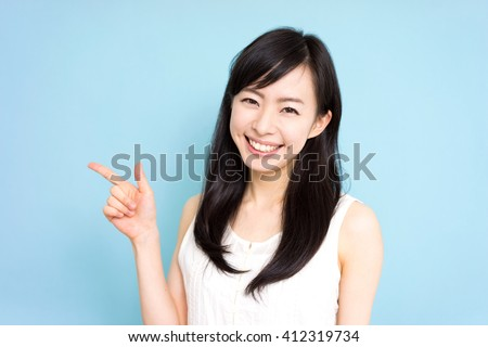 beautiful young woman showing copy space against blue background