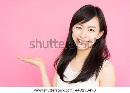 beautiful young woman showing copy space against pink background - stock photo