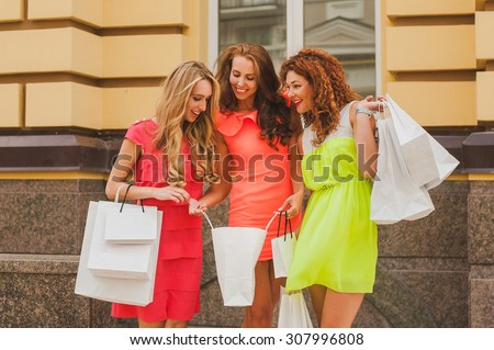 beautiful young woman showing her friends what she got in her shopping bag while sale women in bright dress