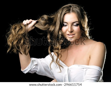 beautiful young woman, showing her long curly hair,  against dark studio background - stock photo