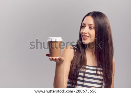 Beautiful young woman showing hot drink in disposable paper cup, isolated over gray background, with copy space - stock photo