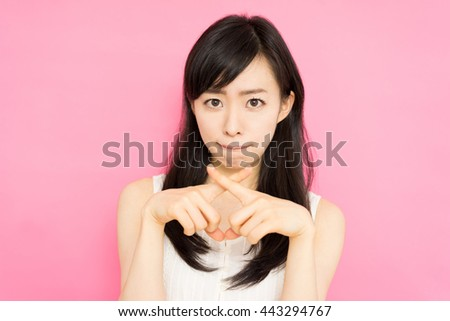 beautiful young woman showing NO gesture against pink background