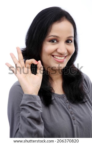 Beautiful young woman showing ok gesture against white - stock photo