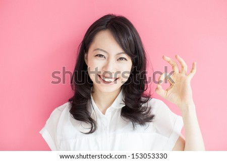 beautiful young woman showing OK sign against pink background  - stock photo