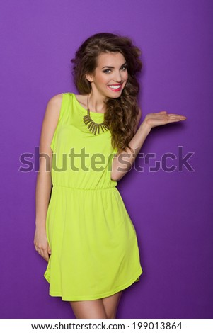 Beautiful young woman showing product. Three quarter length studio shot on violet background. - stock photo