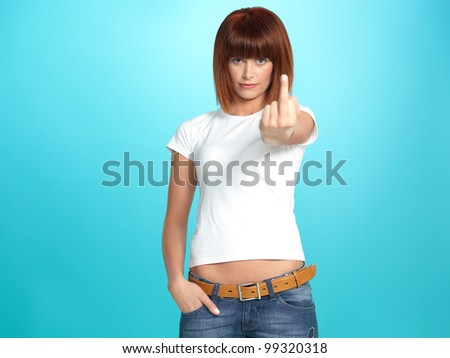 beautiful, young woman showing the middle finger, on blue background - stock photo