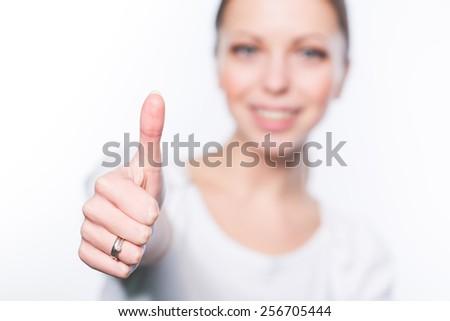 Beautiful young woman showing thumb - stock photo