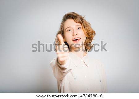 beautiful young woman showing thumbs up, well, close-up, isolated on a gray background
