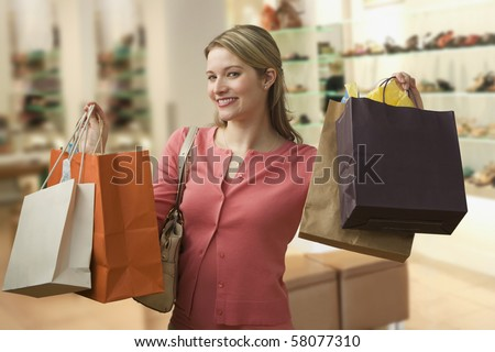 Beautiful young woman shows an ecstatic expression while holding shopping bags in a store.  Horizontal shot. - stock photo