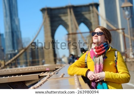 Beautiful young woman sightseeing on Brooklyn Bridge, New York, at sunny spring day - stock photo