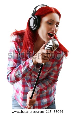 Beautiful young woman singing with microphone isolated on white - stock photo