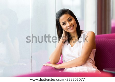 beautiful young woman sitting alone in cafe