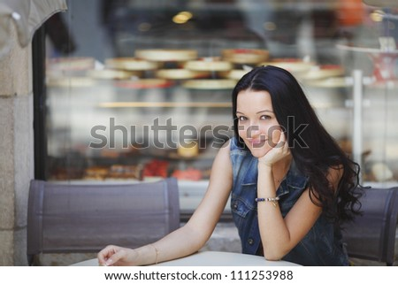 beautiful young woman sitting alone in street cafe - stock photo