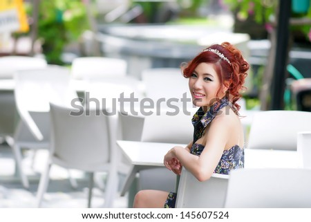 Beautiful young woman sitting alone in street cafe, Model is Thai Ethnicity.