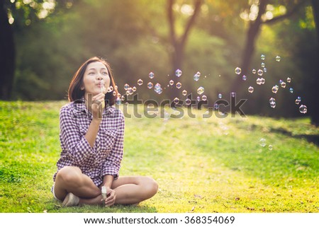 stock photo beautiful young woman sitting and blowing bubble in the park 368354069