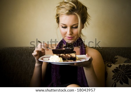 beautiful young woman sitting and eating cake - stock photo