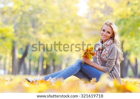 Beautiful young woman sitting and holding bunch of fall leaves in autumn park