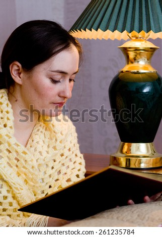 Beautiful young woman sitting and reading book - stock photo