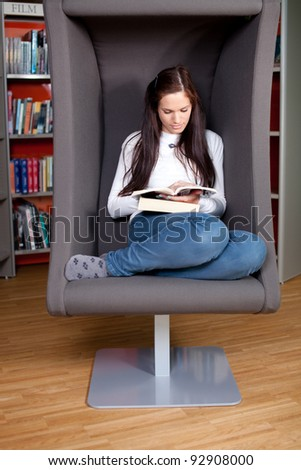 Beautiful young woman sitting and reading in a lounge chair in the library