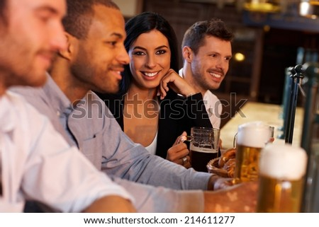 Beautiful young woman sitting at pub with friends, drinking beer. Looking at camera, smiling.