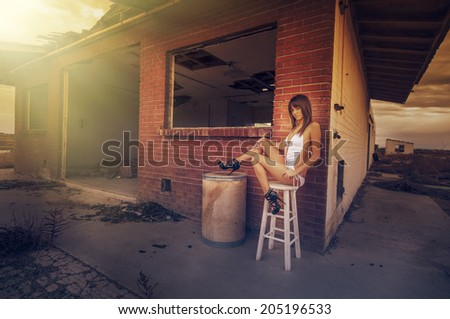 Beautiful young woman sitting beside abandoned old home sunlight shining on her,